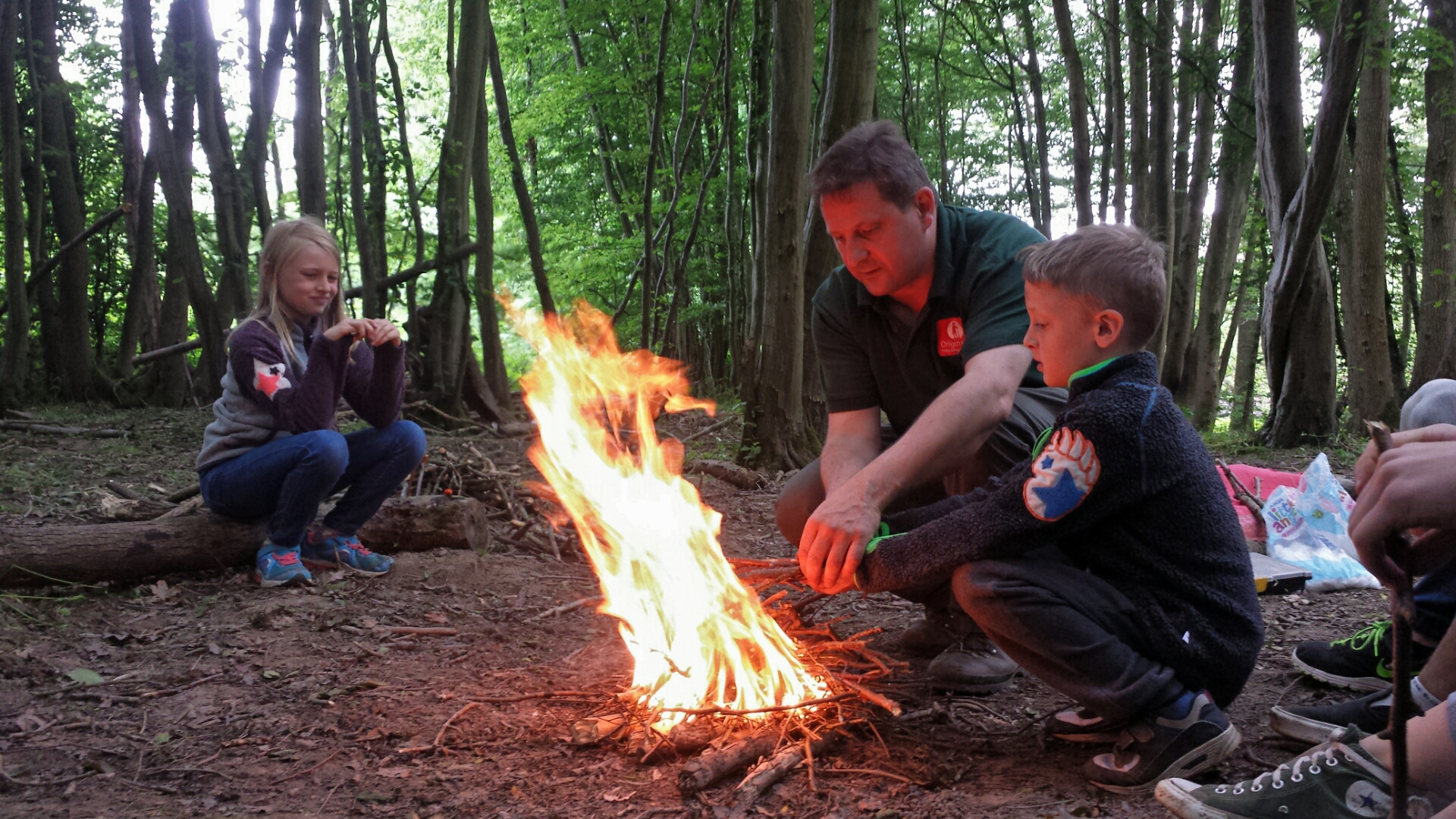 Steve helps a young lad to safely add fuel to the fire, he's positioned himself and the boy in a safe position as the wind is blowing the bright orange flames away from them. A girl watches and waits for her turn to have a go at managing the fire.