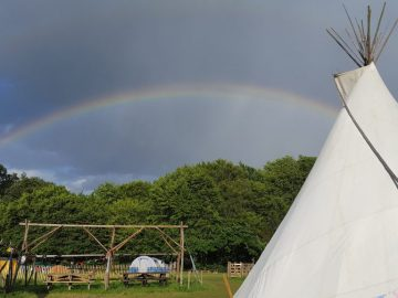 The sun shines even when it rains! A rainbow vivid in the dark and brooding sky above WoWo campsite, the striking white canvas of the tipi is in the righthand side of the picture. A great place to shelter when the weather turns sour and you need a warm place to get cosy next to the fire.