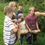 Young children harvesting wild foods for herb bannock bread