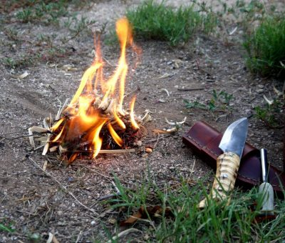 Small fire burning next to a wooden handled bushcraft knife and fire striker which we just used to light the fire