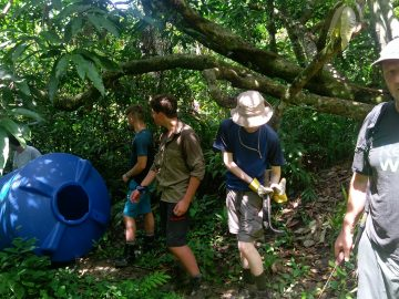 Carrying the water tank through the jungle as a team - the logistics of installing a system in the jungle require the team to work together using each person's strengths.