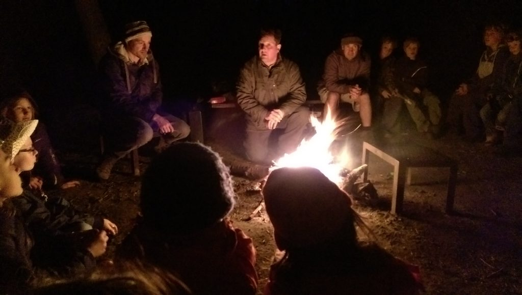 Steve telling one of his tall tales around the campfire; the group is gently illuminated by the light of the fire.