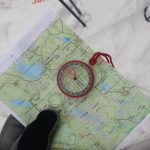 Finding the way... skills to help you navigate in the world and in life. Person holding a map and compass in the snow.