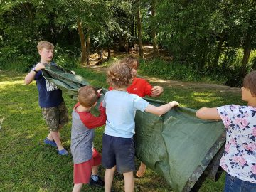 Children folding up a tarpaulin ready to use next time. Being careful with equipment is essential when in a survival situation.
