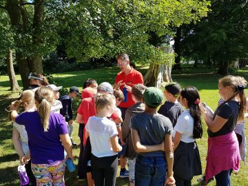 Young People learning about wildlife and surviving from one of the Really Wild Instructors. Nev is describing how important it is to stay hydrated and to keep your water clean and safe.